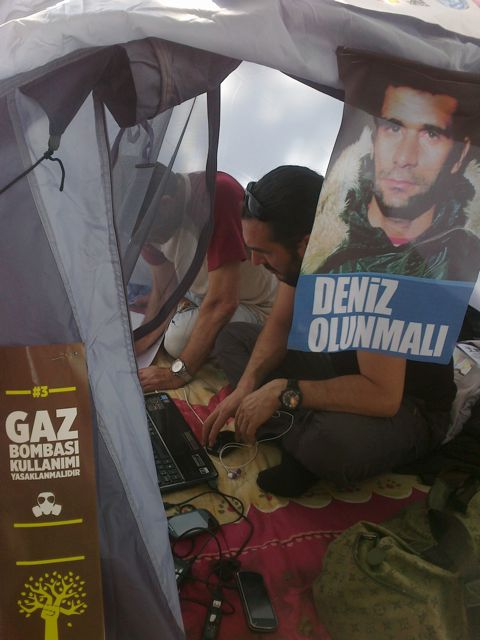 Student activist networks from his tent. Gezi Park now has its own FM radio station too.