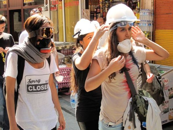 Middle-class girls fix their gear as they try to find a way past police lines to recover Taksim.
