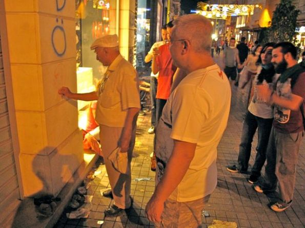 Group claps as an old man draws a picture on the wall of the Paşabahçe glassware shop of republican founder