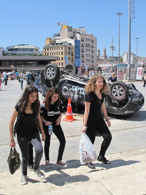 Another overturned car on Taksim Square, quite a contrast to a typical group of well-brought-up girl protestors, wearing the signature black of the protests.