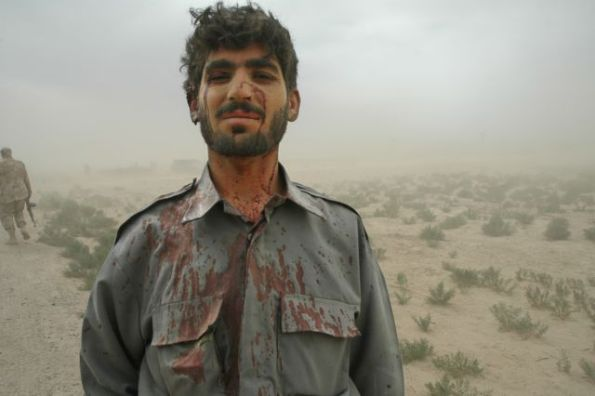 """I survived"" - Afghan soldier standing to attention after a suicide bombing nearby. Photo by Graeme Smith"